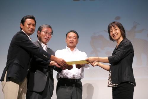 逗子市の認定式(2017年8月)では、認定証を(写真左から)逗子市長、逗子フェアトレードタウンの会代表、逗子市議の3名が受け取り、3者の協力で認定が実現したことをアピール。右は日本フェアトレード・フォーラム代表